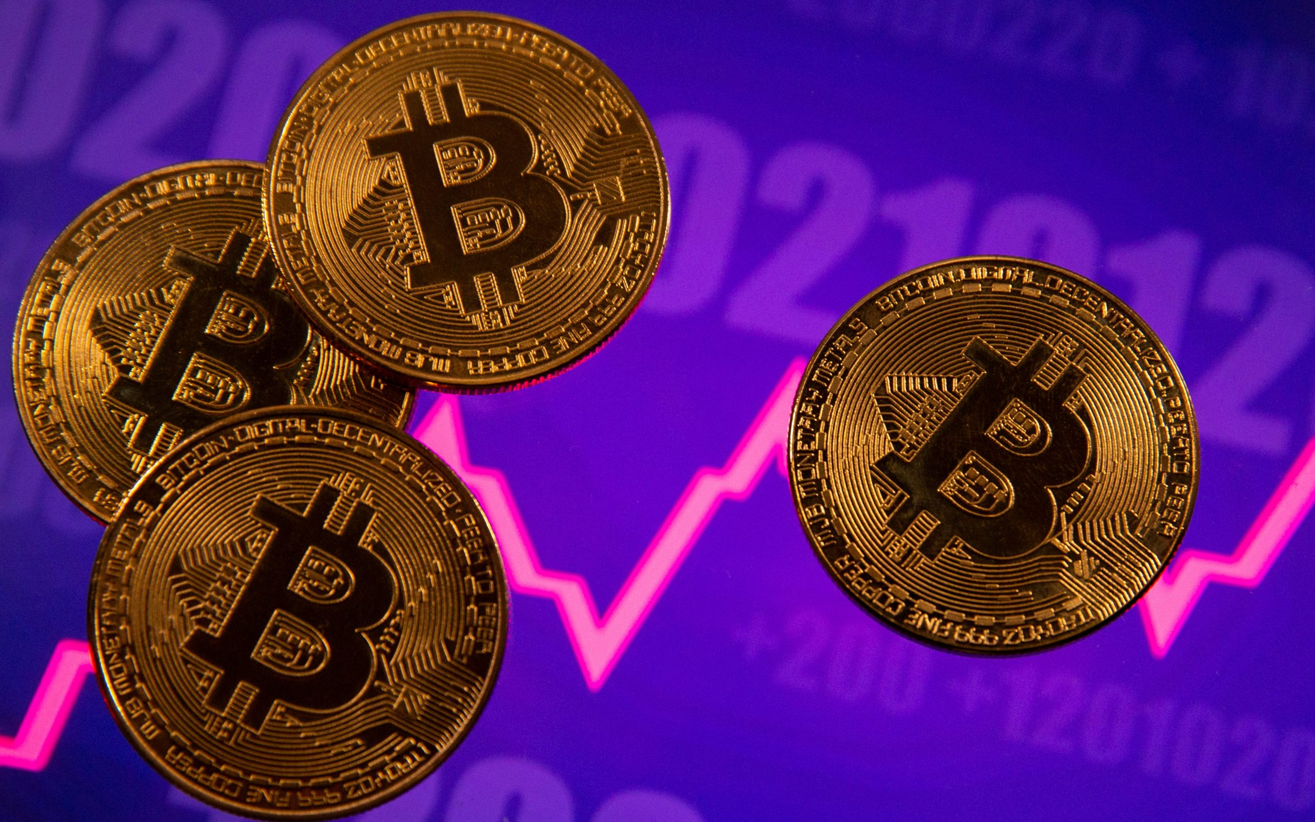 A representation of virtual currency Bitcoin is seen in front of a stock graph in this illustration taken March 15, 2021. REUTERS/Dado Ruvic