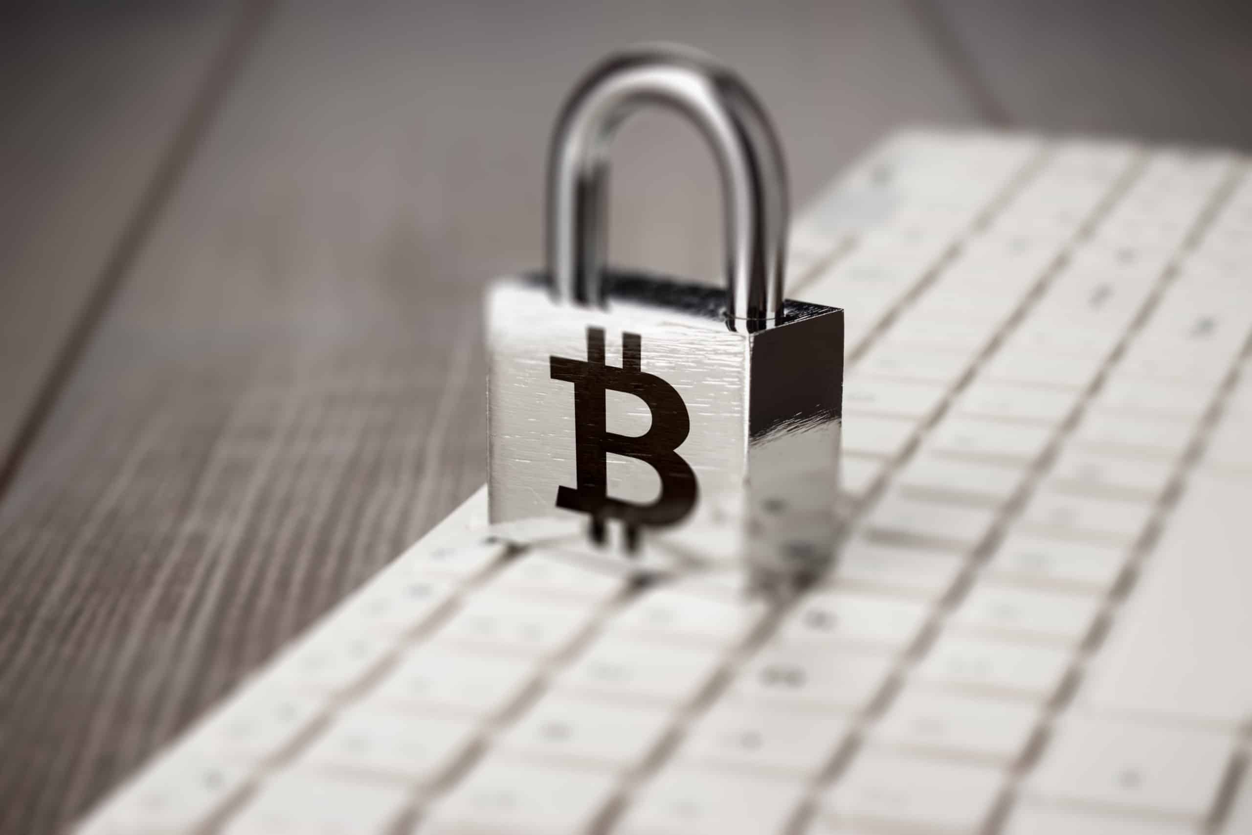 Padlock with bitcoin symbol over a keyboard, blockchain has cyperspace risks