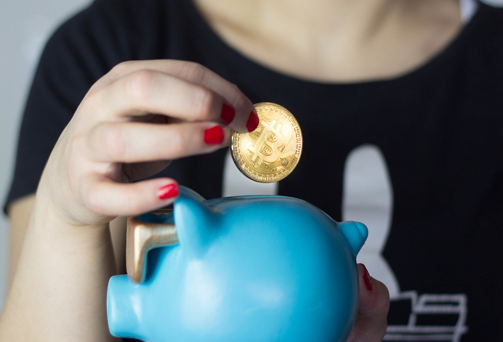 Picture of a hand putting a bitcoin in a piggybank